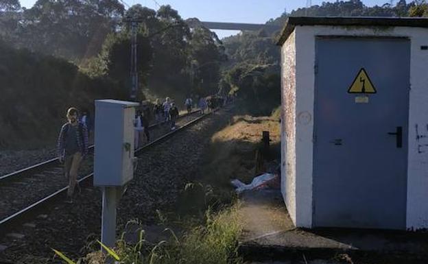 Pasajeros caminan por las vías en el tramo Villabona-Avilés.